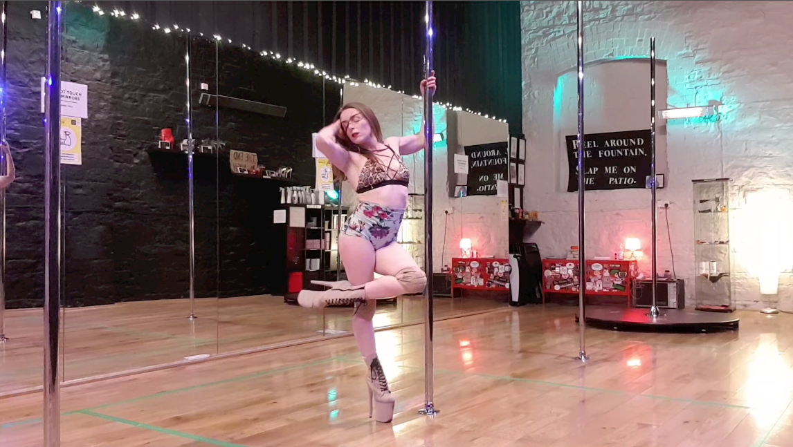 Arlene posing with the pole while dancing
