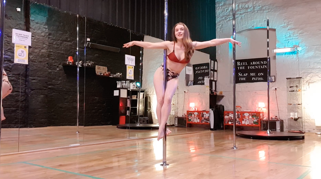 arlene demonstrating the front crucifix pole trick