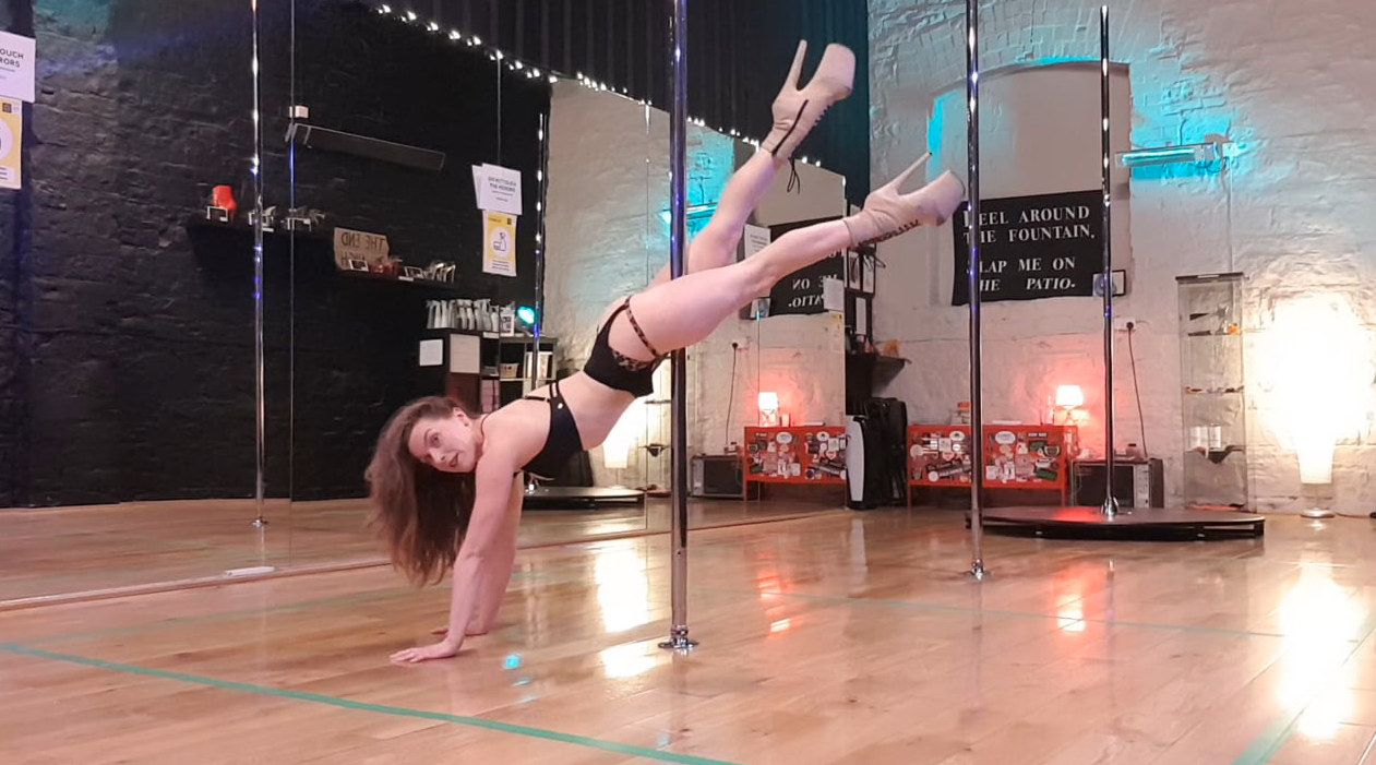Arlene demonstrating plank body rolls on the pole