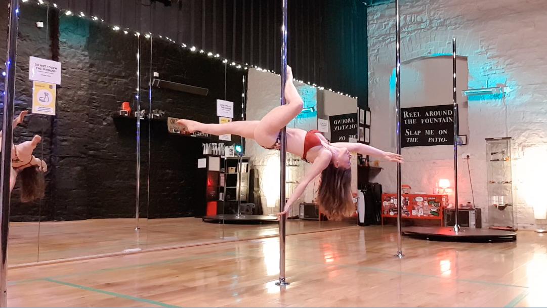Arlene demonstrating flatline scorpio trick on the pole