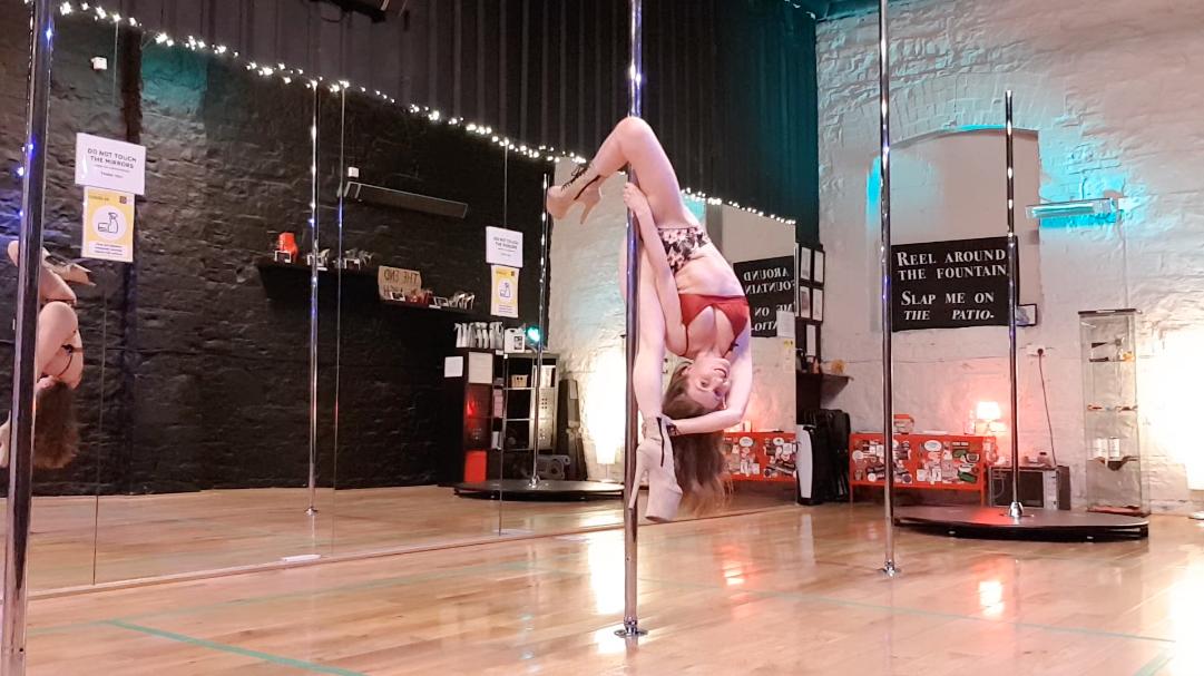 Arlene demonstrating genie split trick on the pole